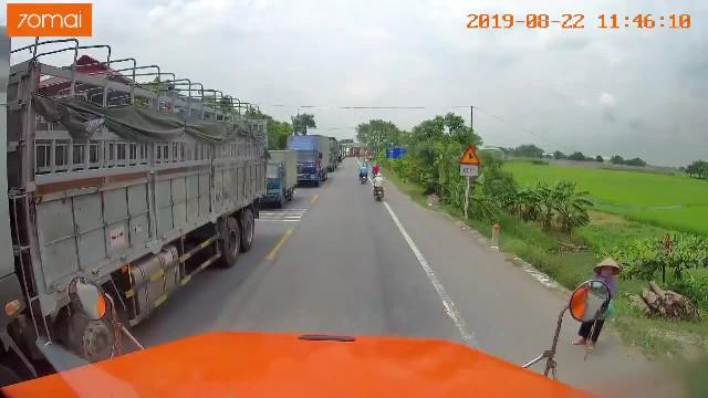 Tài xế container dừng xe dắt cụ bà qua đường